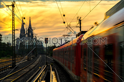 Train moving in a direction toward DOM church in cologne, germany sunset time. Cologne DOM one of the most famous church in all of Europe.