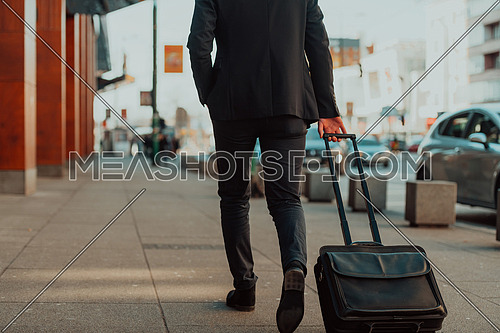 Came To Airport. Man Traveller Walking With Suitcase Outdoors And Using Smartphone. High-quality photo