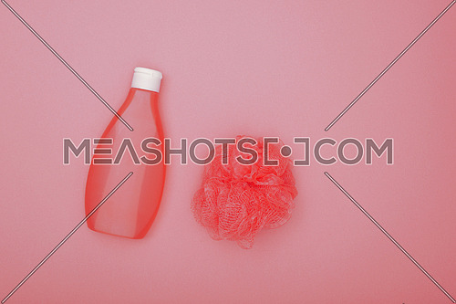 Close up one bottle of shower gel and feminine soft bath skin scrub puff over pink background, elevated top view, directly above