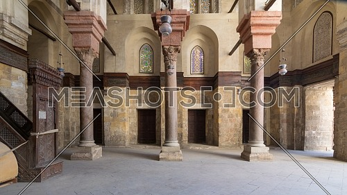 Interior of Sultan Qalawun public historic mosque with stone columns, colored stained glass windows and wooden doors, Cairo, Egypt