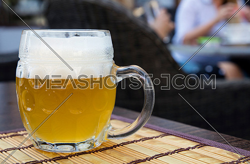 One glass mug of unfiltered craft draft white wheat weizen beer on wooden bamboo mat on table, close up, people at background