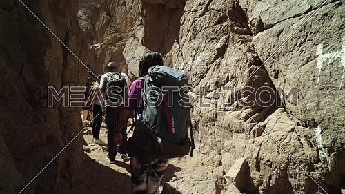 Follow shot for group of tourists walk into a rocky groove with bedouin guide exploring Sinai Mountain for wadi Freij at day.