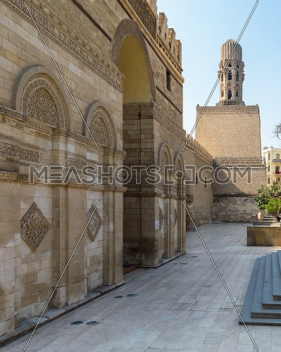 Entrance of public historic Al Hakim Mosque known as The Enlightened Mosque with Minaret in the far end, located in Moez Street, Old Cairo, Egypt