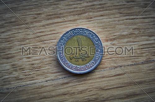 close up for One Egyptian pound coin on Number side with wooden background