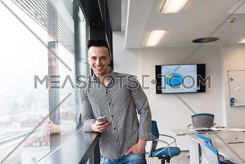 relaxed young businessman using smart phone at modern startup business office meeting room  with big window and city in backgronud