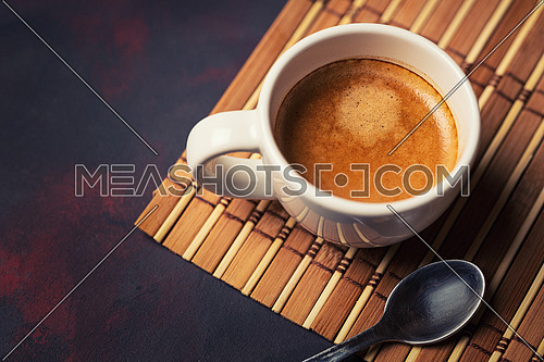 White cup of coffee and teaspoon on dark background. Copy space. Top view.