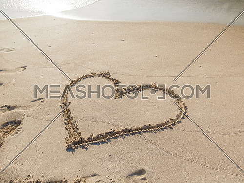 Love sign written on sand on a beach