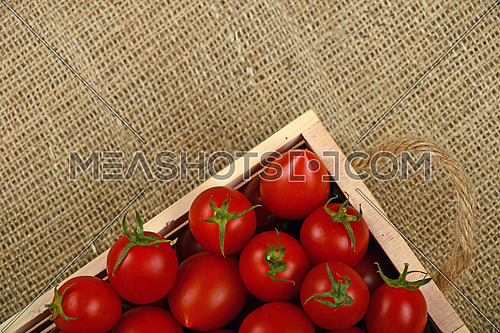 Red ripe fresh cherry tomatoes in small wooden box with twine jute handles on burlap canvas background, top view