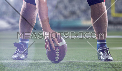 Closeup of american football player preparing to start the football game on american football field at modern stadium with lights and flares at night