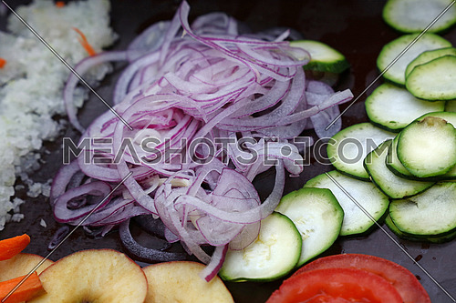 Close up assorted cut and sliced fresh vegetables on black cooking board, high angle view