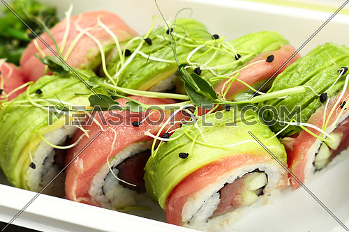 Close up take away set of six raw tuna and avocado sushi rolls in disposable white plastic tray, high angle view