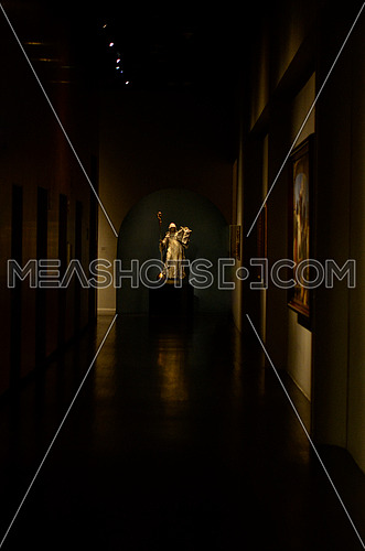 A hallway in a museum with a statue in the end of the hall