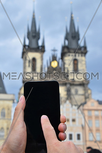 Close up man hands with smartphone taking picture of old town cityscape with Cathedral of Our Lady before Tyn, Prague, Czech Republic