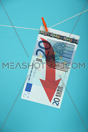 European economy crisis, decline of Euro currency, twenty Euro banknote with red arrow down hanged descending with pin at rope over blue background