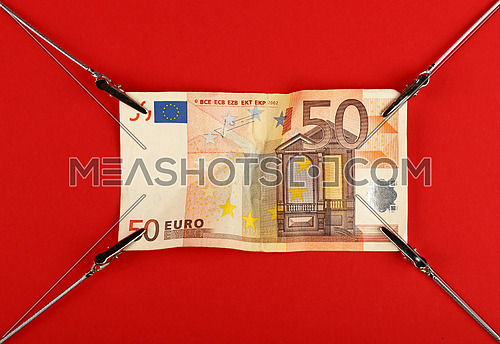 Close up one fifty Euro paper currency banknote pulled and stretched over red background with copy space, high angle view
