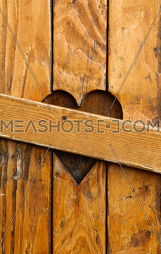 Close up closed wooden window shutters with one heart shape as symbol of divorce, broken heart and love problems