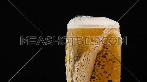 Close up background of pouring lager beer with bubbles and froth in glass over black background, overfill and run out, flowing over the top, low angle