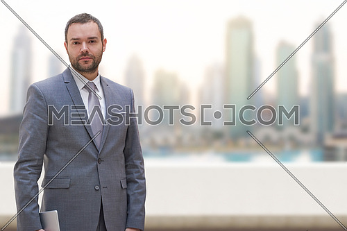 Portrait of young businessman standing on balcony in front of the big city
