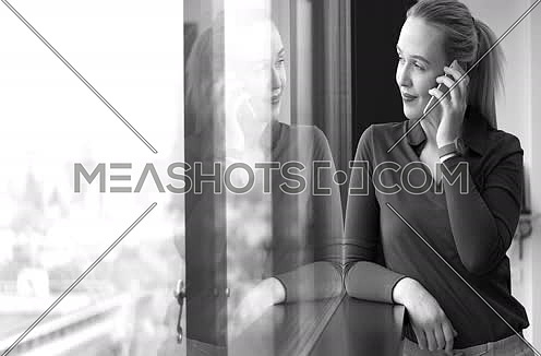 Elegant Woman Using Mobile Phone by window in office building