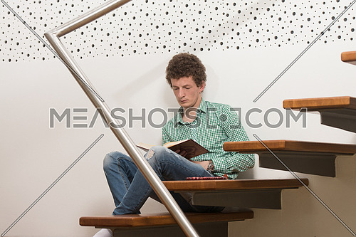 Young Muslim Man Is Reading The Koran In The Mosque - Afro Lock Hair Curly