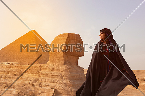 egyptian woman in traditional bedouin clothes in front of ancient great giza pyramids  and sphinx profile