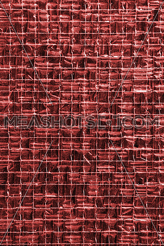Background texture of red stained glass reinforced with metal wire mesh grid, close up