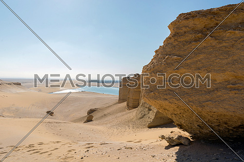 Footprints in sand desert with rick sides with under way lake view in sunlight blue sky , Fayoum , Egypt