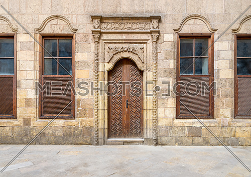 Facade of old abandoned stone decorated bricks wall with arched wooden door and four wooden shutter windows