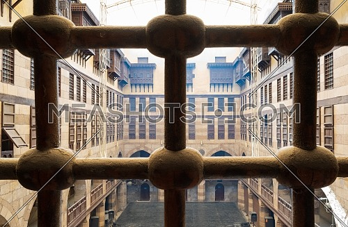 View of the courtyard of caravansary (Wikala) of al-Ghuri through window with iron ornate grid, showing vaulted arcades and interleaved wooden grids (mashrabiya), Cairo, Egypt
