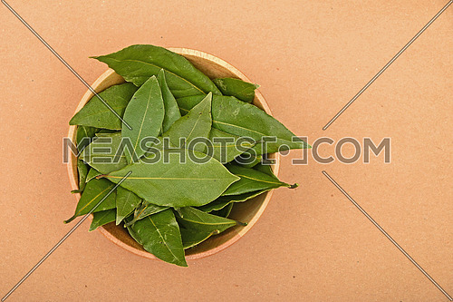 Wooden bowl of green bay laurel leaves on brown kraft paperbackground