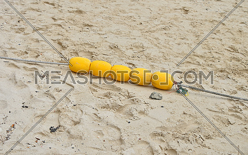 Four yellow polystyrene sea marker buoys group with cable tow on wet sand sea beach