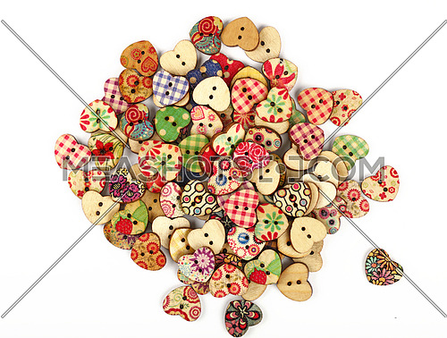 Vintage heart shaped painted wooden handmade sewing buttons isolated on white, close up, elevated top view