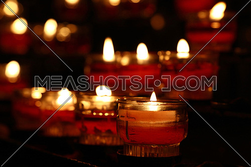 Red glass translucent candles burning in dark church, close up, low angle view