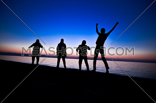 A group of four friends standing by the beach jumping at having fun at sunset magic hour