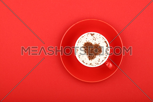 Close up one latte cappuccino coffee with heart shaped chocolate milk topping in red cup with saucer over background of red paper, elevated top view, directly above