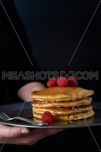 Female hands serving pan cakes with red berries