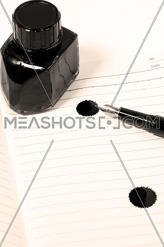 classic black fountain pen on open notebook with ink bottle with stain on page,sepia filter