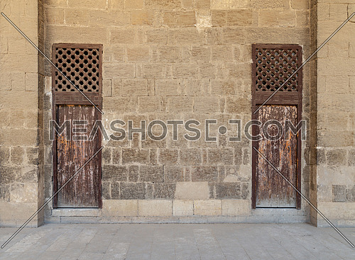 Facade of old abandoned stone bricks wall with two weathered wooden doors and windows covered with wooden grid, Old Cairo, Egypt