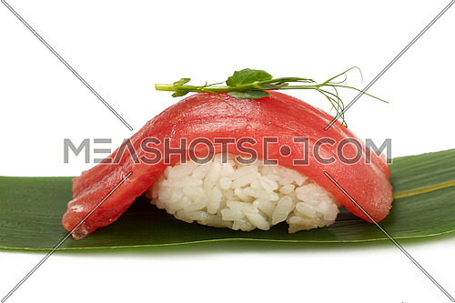Close up one nigiri sushi with tuna fish served on fresh green banana leaf isolated on white background, low angle side view