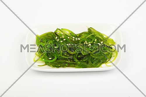 Portion of Asian traditional greed marinated seaweed salad appetizer on small white dish plate over white background, high angle view