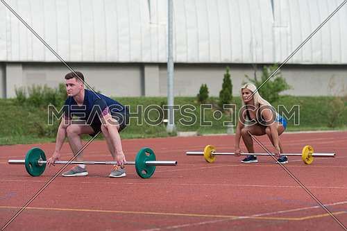A Group Of Young People In Aerobics Class Doing A Bent Over Barbell Row Exercise Outdoor