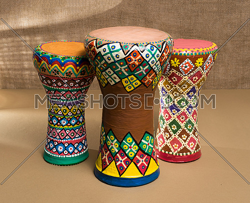 Front view of three decorated colorful pottery goblet drums (chalice drum, tarabuka, darbuka) on background of wooden table, and sackcloth wall