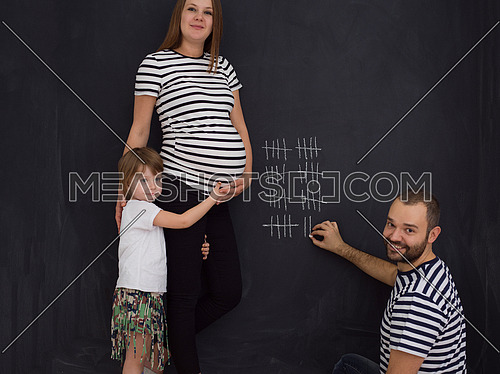 young pregnant couple with cute little daughter accounts week of pregnancy and writing them with chalk on blackboard