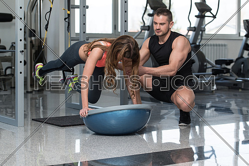 Personal Trainer Showing Young Woman How To Train With Trx Fitness Straps In A Health And Fitness Concept