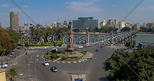 Drone Shot flying beside Cairo Opera House Backwards from Saad Zaghloul Statue showing Qasr Al Nile Bridge and Nile Ritz Carlton Hotel in background then move Left Across the River Nile to Hilton Ramses Hotel at day time