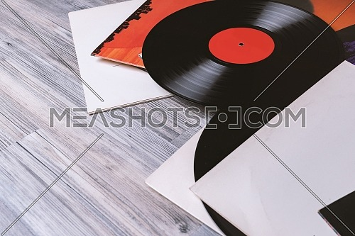 Black vinyl record and covers album on the background of their gray wooden boards.Vintage style with copy space.