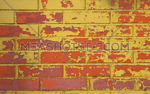 Old grunge red brick wall painted with yellow paint with flakes, stains and defects