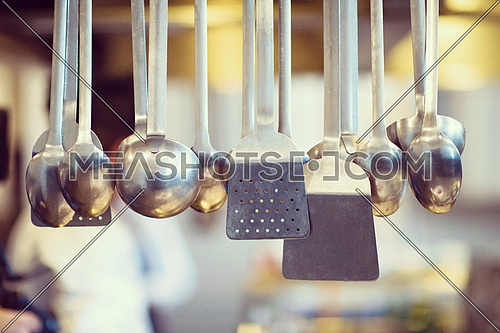 professional Cooking utensils hanging in a restaurant kitchen