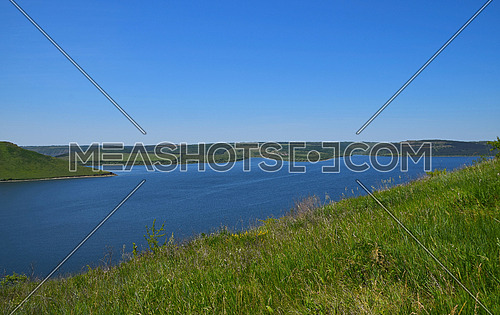 Beautiful vivid riverside landscape with high river banks, green hills, blue sky and rippled water in day time, view from another bank