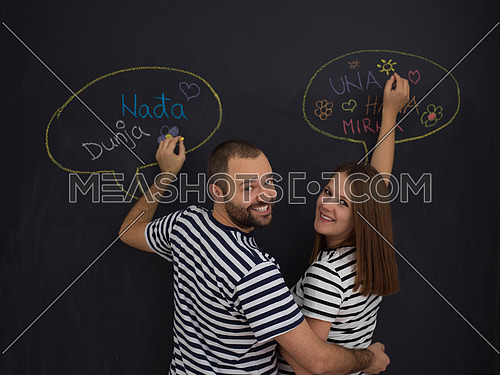 young pregnant couple thinking about names for their unborn baby and writing them on a black chalkboard